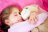 Girl sleeping with teddy bear — Stock Photo