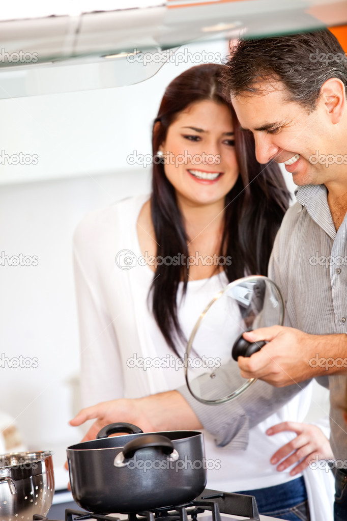 Loving couple in the kitchen cooking at home — Stock Photo #9664824