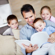 Stock Photo: Father reading to children
