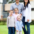Family standing outside house - Stock Photo