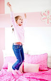 Girl jumping on the bed — Stock Photo