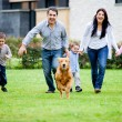 Family running with dog — Stock Photo