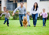 Family running with dog — Stok fotoğraf