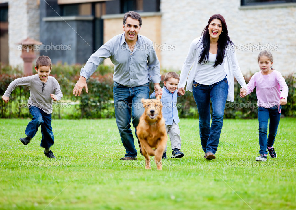 Happy family running with their dog outdoors  Stock Photo #9774135
