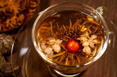 Blooming tea with red and white flower close up in a cup — Stock Photo