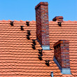 Red tiles roof and bricks chimney on blue sky — Stock Photo