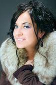 Portrait of beauty woman smilie, fur, makeup, dark hair, studio shot — Stock Photo