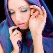 Beauty woman face in blue cloth and makeup, studio shot on dark background — Stock Photo