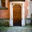 Wooden church door with stone and brick wall surround - Stock Photo