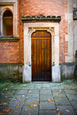 Wooden church door with stone and brick wall surround — Stock Photo