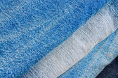 Stack of various shades of blue jeans trousers as texture or background to — Stock Photo