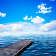 Wooden jar, pier on an ocean in summer view of sunny day, blue sky and whit - Стоковая фотография