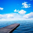 Wooden jar, pier on an ocean in summer view of sunny day, blue sky and whit - Photo
