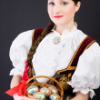 Beauty woman in traditional Polish clothes holding wicker basket with Easter eggs, Cieszyn Silesia region, studio shot — Stock Photo #9328092