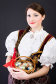 Beauty woman in traditional Polish clothes holding wicker basket with Easter eggs, Cieszyn Silesia region, studio shot — Stock Photo