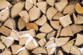 Background. A woodpile of dry fire wood in the winter. — Stock Photo