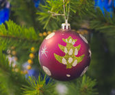 The Christmas-tree decoration in the form of purpur ball. — Stock Photo