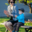 Young mother and her son sitting on bench — Stock Photo #10560225