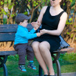 Young mother and her son sitting on bench — Stock Photo