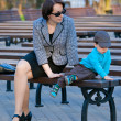 Mother and son sitting outdoors — Stock Photo #10560230