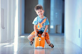 Cute three years old boy sitting on a suitcase — Stock Photo