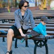 Mother and son sitting outdoors — Stock Photo