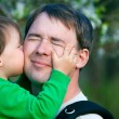 Little son kissing his father outdoors — Stock Photo