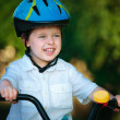 Portrait of a cute little boy in a bicycle — Stock Photo