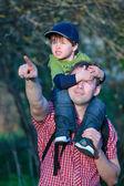 Cute little boy sitting on father's shoulders — Foto de Stock