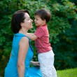 Two years old boy hugs his young mom in park — Стоковое фото