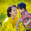 Mother and little child on yellow meadow — Stock Photo #10667593