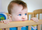 Baby Boy chomps his wooden bed — Stock Photo