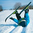 Young boy with cross-country skis lying on snow — Stock Photo