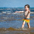 A cute little boy running through the water at the beach — Stock Photo