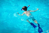 A little boy diving under water surface in a swimming pool — Stock Photo
