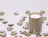 Decoration from burning candle and stars in silver — Stock Photo