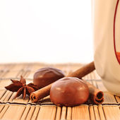 Cup, chocolates and spices — Stock Photo