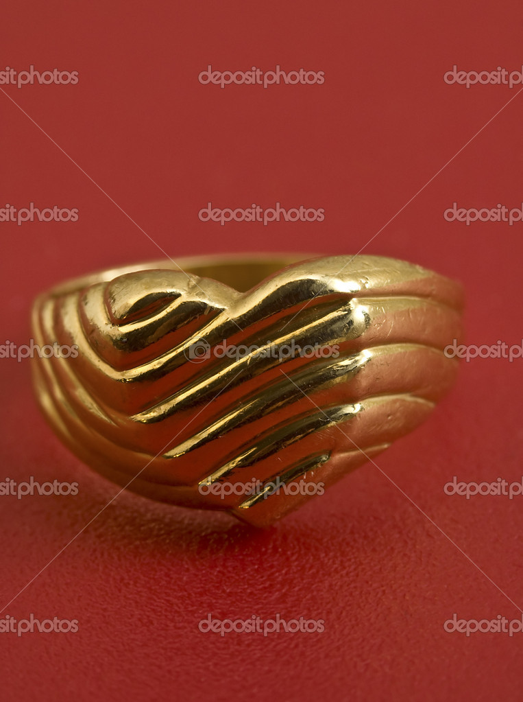Golden heart ring on a red background, vertical photo  Stock Photo #10367899