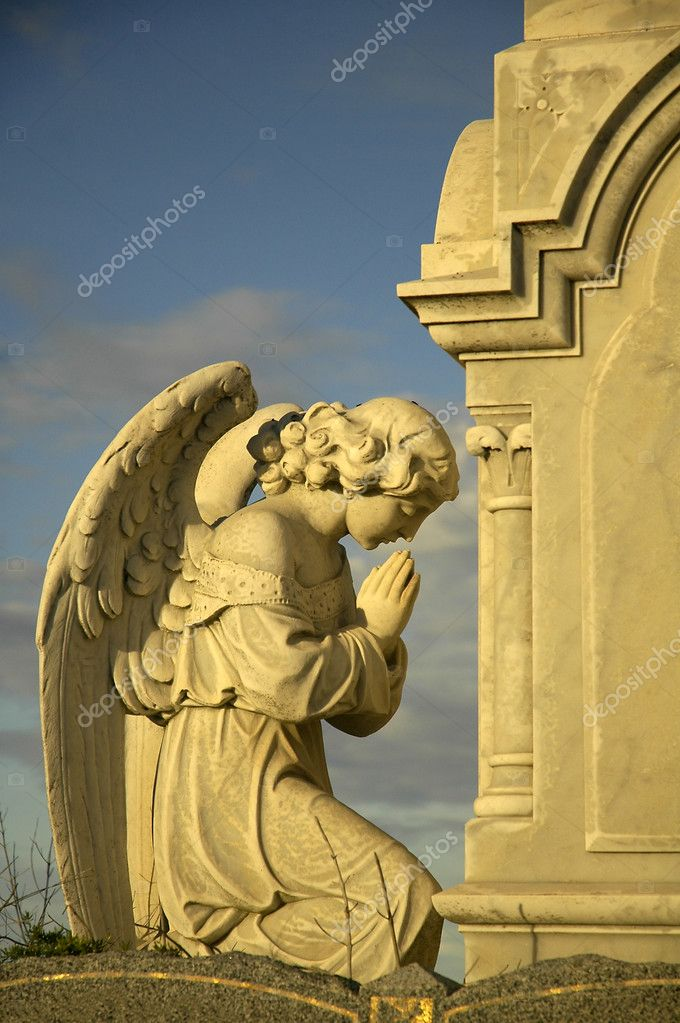 Angel sculpture praying in front of stone tomb, yellow dusk sun  Stock Photo #8226168