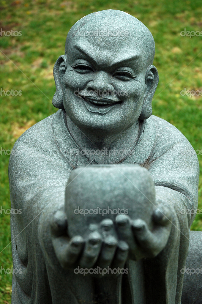 Stone buddha sculpture offering a cup and smiling, grass in background — Stock Photo #8226476