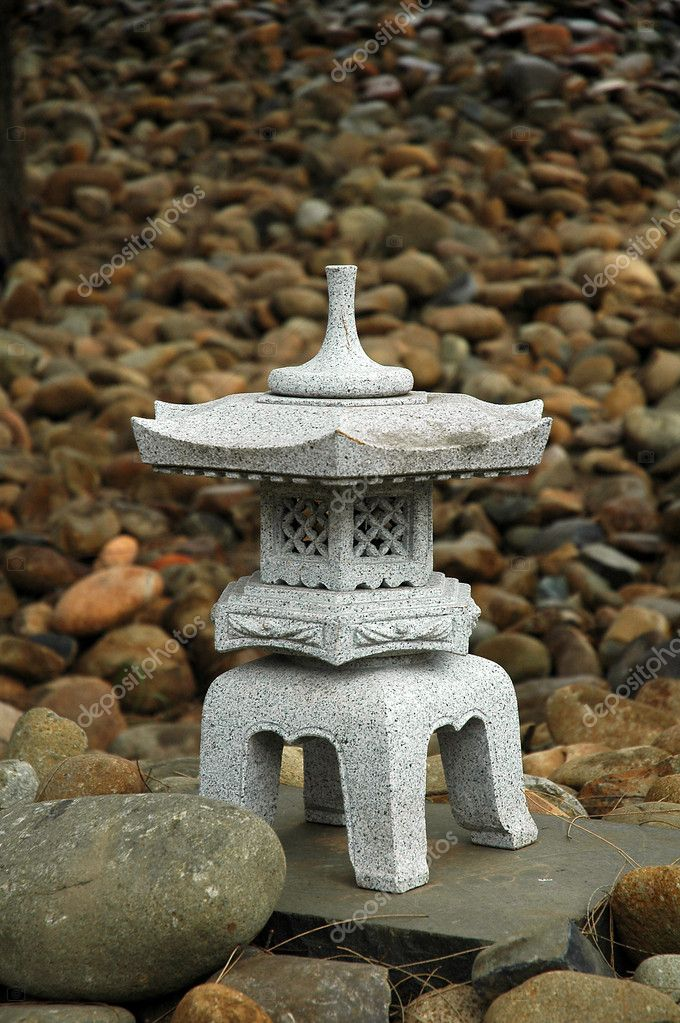 Small buddhist sculpture made of stone, small stones in background — Stock Photo #8365524