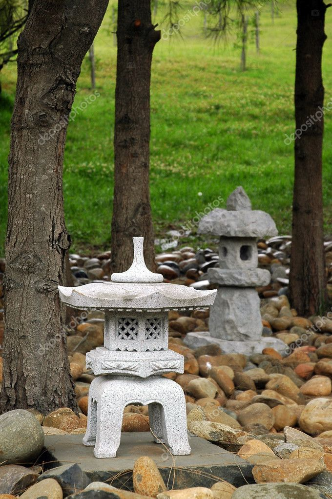 Small buddhist sculptures made of stone, small stones, green grass, and trees in background — Stock Photo #8365615