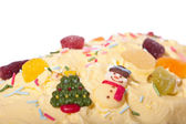 Christmas cake decorated with icing, christmas tree, iceman and other sweets — Stock Photo