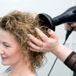Stylist drying woman hair — Foto Stock