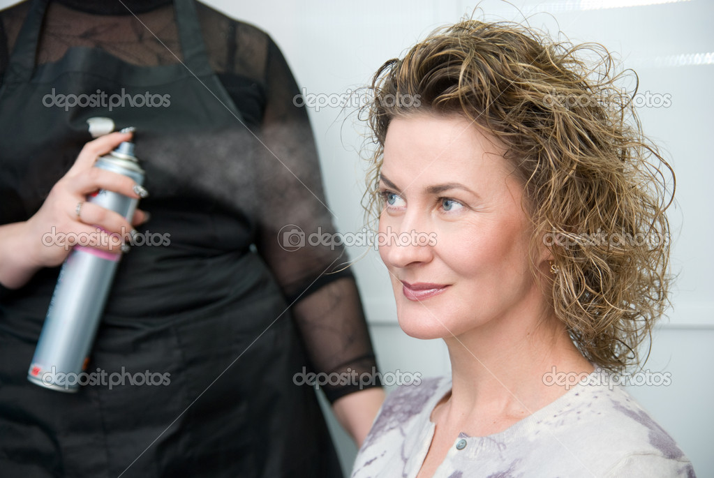 Hairdresser fixing woman hair with hairspray  in hairdresser salon — Stock Photo #10412044