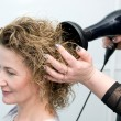 Stock Photo: Stylist drying woman hair