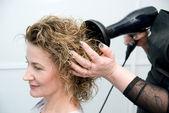 Stylist drying woman hair — Stock Photo