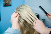 Hairdresser makes hair styling for woman by rake-comb — Stock Photo