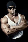 Strong athletic man in dark glasses — Stock Photo
