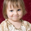 Portrait of the nice little girl on a red background — Stock Photo